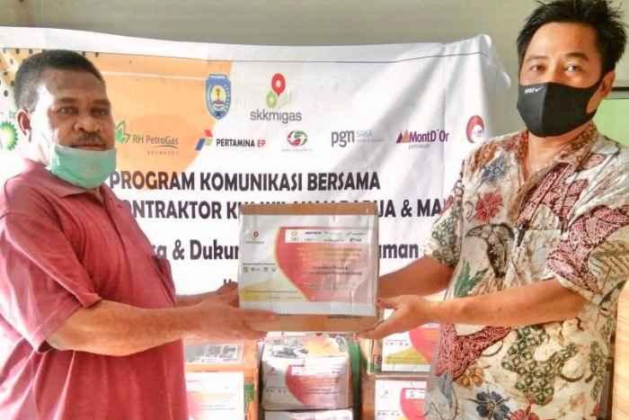 Serah terima Paket Komunikasi dan Dukungan JPS dari pelaksana kegiatan, Bpk Samuel Wailola (kanan) kepada Ketua Klasis GKI Bintuni, Pdt. S.Awi (kiri). Foto ; SKK Migas Pamalu.