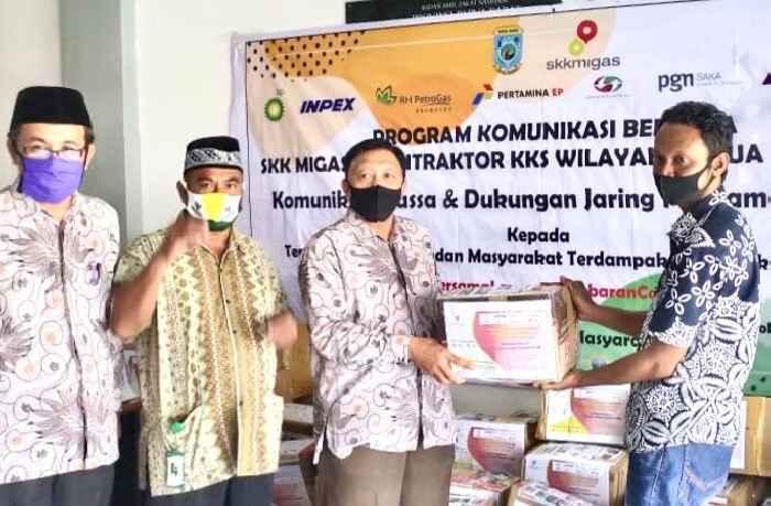 Wakil Ketua Baznas Manokwari, Sali Pelu (kiri), menerima bantuan dari Lewi Junot (kanan), Tim koordinator pelaksana kegiatan SKK Migas di Manokwari. Foto; SKK Migas Pamalu.